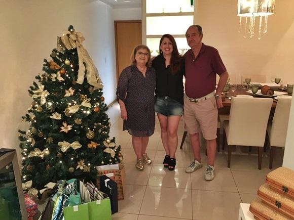 Érika no meio da mãe e do pai, ao lado de uma árvore de Natal com presentes