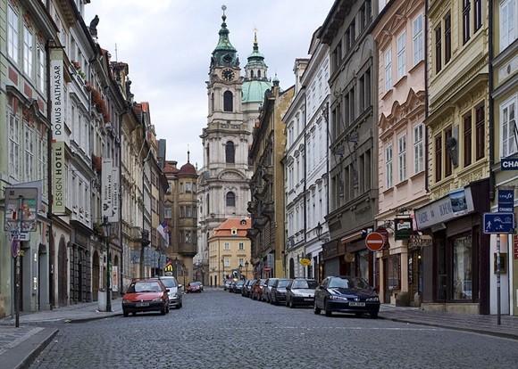 Rua do bairro Malá Strana com torre ao fundo Blog Vem Por Aqui