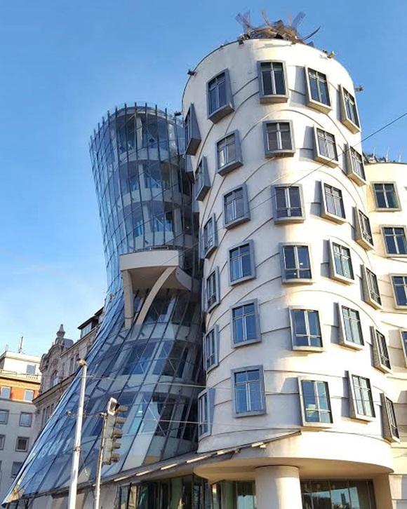 Foto dos prédios dançantes, com torre redonda e outra de vidro, torta, simulando uma casal dançando Blog Vem Por Aqui