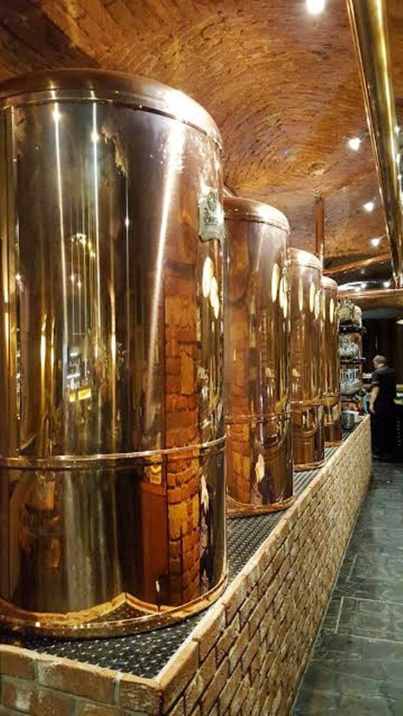 Toneis de cobre de Pilsner Urquell dentro do bar Bog Vem Por Aqui