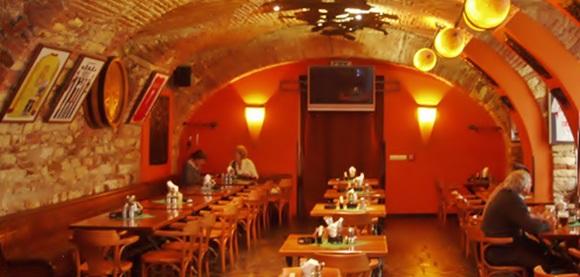 Salão interno do Bredovsky Dvur com teto ovalado, paredes de tijolinho e mesas de madeira nos cantos e no centro Blog Vem Por Aqui