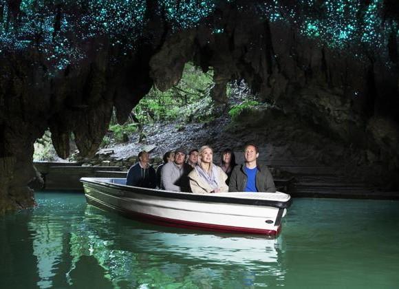 Barco na entrada da caverna com turistas olhando o começo do céu iluminado Blog Vem Por Aqui