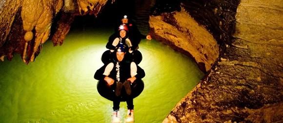 Pessoas sentadas num pneu fazendo rafting na caverna e águas esverdeadas pelas luzes das lanternas Blog Vem Por Aqui