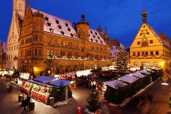 Barraquinhas da feira de natal iluminadas em frente aos prédios da praça principal de Rotemburgo Blog Vem Por Aqui