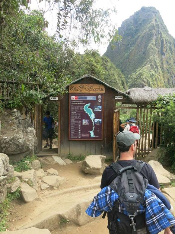 Uma das entradas para Machu Picchu em madeira com porta estreita e pessoas passando Blog Vem Por Aqui