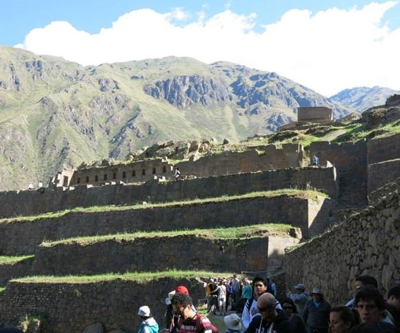 Degraus de uma das escadarias de Machu Picchu com turistas na parte de baixo e montanhas sob céu azul com nuvens acima Blog Vem Por Aqui