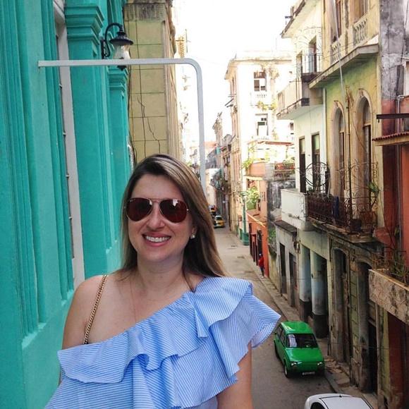 Sana numa varanda de um prédio em Havana com rua ao fundo e outro prédio ao lado Blog Vem Por Aqui