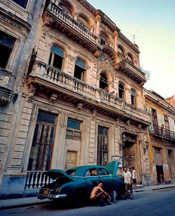 Prédio antigo de Havana com carro com defeito e homens diante dele na frente Blog Vem Por Aqui