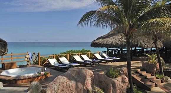 Área de ofuro no hotel com espriguiçadeiras e palmeira na entrada Blog Vem Por Aqui