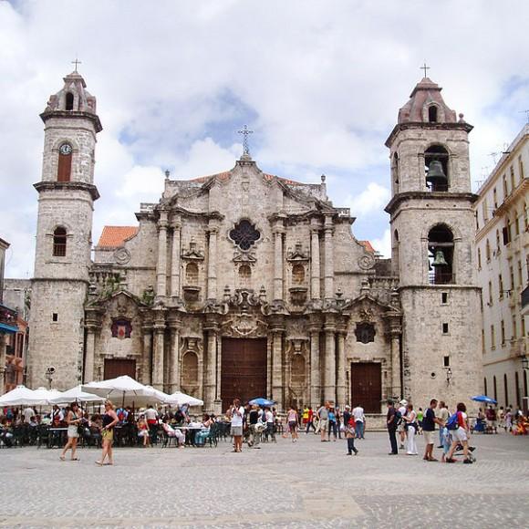 Catedral de Havana com turistas passeando na frente e sentados em mesinhas de bares ao lado Blog Vem Por Aqui