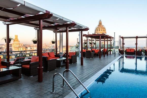 Vista da piscina do hotel com poltronas e mesinhas ao lado
