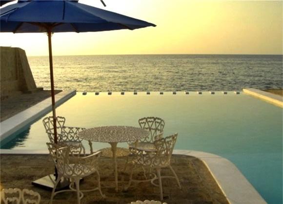Mesa de ferro embaixo de um guarda-sol, piscina do Vistamar e mar ao fundo Blog Vem Por Aqui