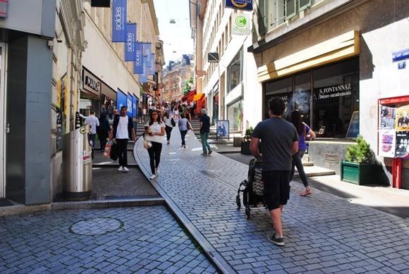 Marido de Teresa de costas, andando com o carrinho na direção de uma ladeira e outras pessoas passando na rua Blog Vem Por Aqui