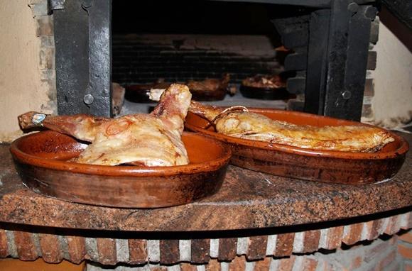 Duas peças de cordeiro dentro das travessas de barro em frente ao forno à lenha Blog Vem Por Aqui