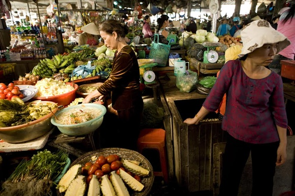 Mercado de Hoi An com frutas e verduras nas barracas e duas mulheres dentro de uma delas Blog Vem Por Aqui