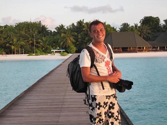 Marco Pomarico em pé numa ponte de madeira em cima do mar com uma mochila nas costas e a câmera na frente Blog Vem Por Aqui