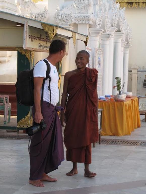 Marco de lado conversando com um monge budista com a câmera na mão e vestindo um sarongue Blog Vem Por Aqui