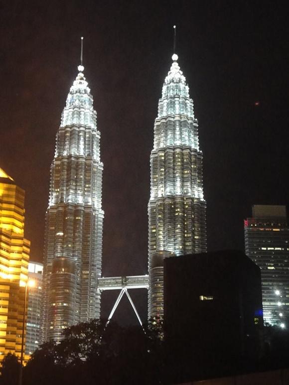 Torre Petronas iluminada à noite Blog Vem Por Aqui