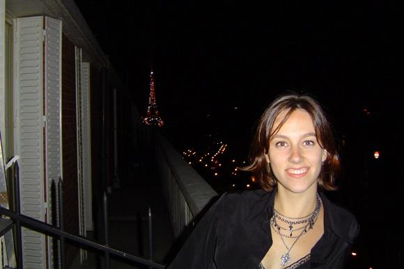 Maria Teresa na sacada do apartamento com a Torre Eiffel ao fundo Blog Vem Por Aqui