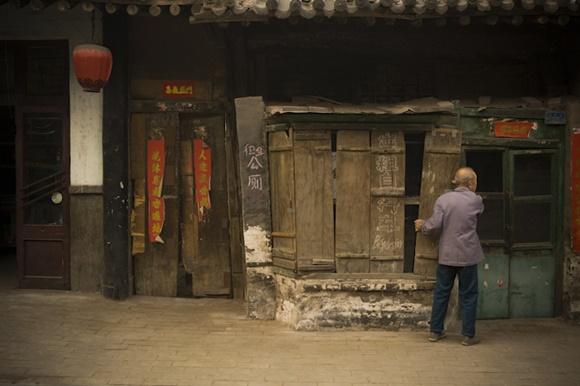 Senhor colocando uma tábua num casebre em Ping Yao Blog Vem Por Aqui