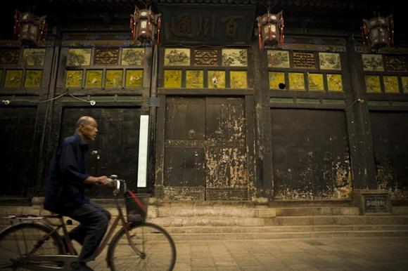 Senhor passando de bicicleta em frente a um prédio antigo com portas de madeira gastas Blog Vem Por Aqui