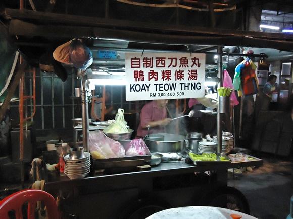 Barraquinha de comida à noite, na rua Blog Vem Por Aqui