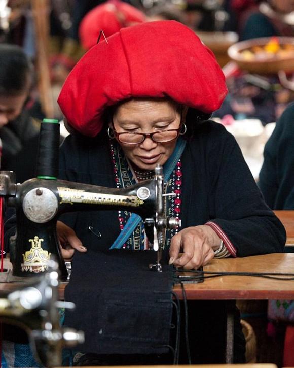 Senhora com trajes típicos costurando na máquina Blog Vem Por Aqui