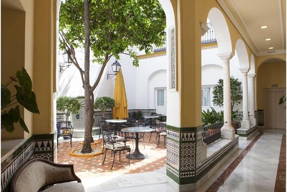 Corredor com pilastras com azulejo colorido patio ao fundo Blog Vem Por Aqui