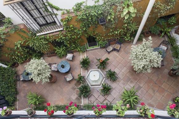 Vista de cima do pátio com mesinhas e plantas em cima do piso de azulejo Blog Vem Por Aqui