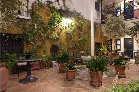 Plantas espalhadas pelo pátio e porta de um dos quartos ao fundo. Luz acesa no topo de uma parede Blog Vem Por Aqui