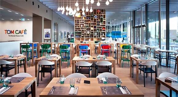 Parte interna do café com letreiro com letras coloridas, mesas e mosaico de estante ao fundo Blog Vem Por Aqui