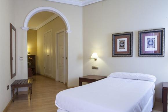 Quarto do hotel com cama coberta com lençol branco e dois quadros acima, ao fundo, arco que dá para a porta e outras dependências
