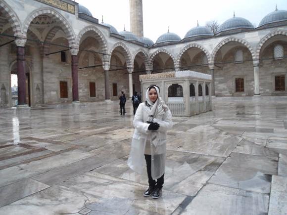 Paula de capa de chuva no meio do pátio da mesquita Blog Vem Por Aqui