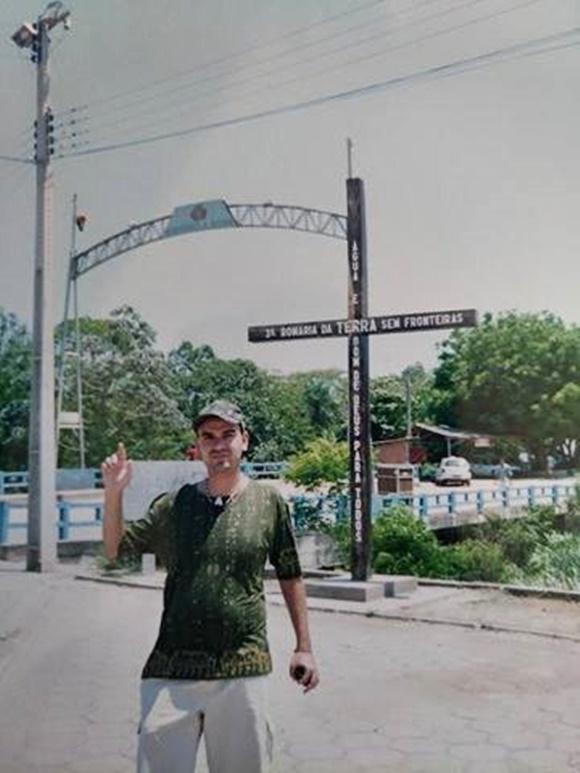 """Fred na fronteira entre Brasil e Bolívia apontando para a placa que diz """"Bienvenido a Bolivia"""" Blog Vem Por Aqui"""