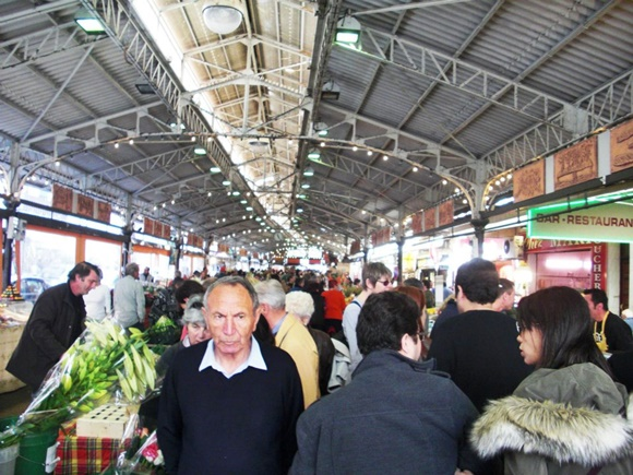 Entrada do mercado com várias pessoas andando e barraquinhas nas laterais Blog Vem Por Aqui