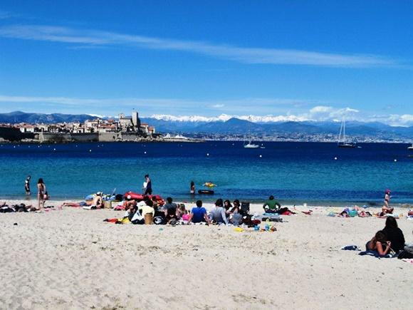 Praia de Antibes com areia branca, pessoas deitadas, mar azul e alpes no fundo Blog Vem Por Aqui