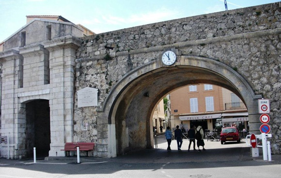 Pórtico da muralha com relógio no topo e vista para uma pequena rua com pessoas entrando Blog Vem Por Aqui