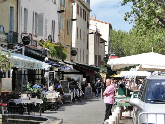 Trecho da rua com vários bares marcados por toldos, placas com cardápio e mesas e cadeiras nas calçadas Blog Vem Por Aqui