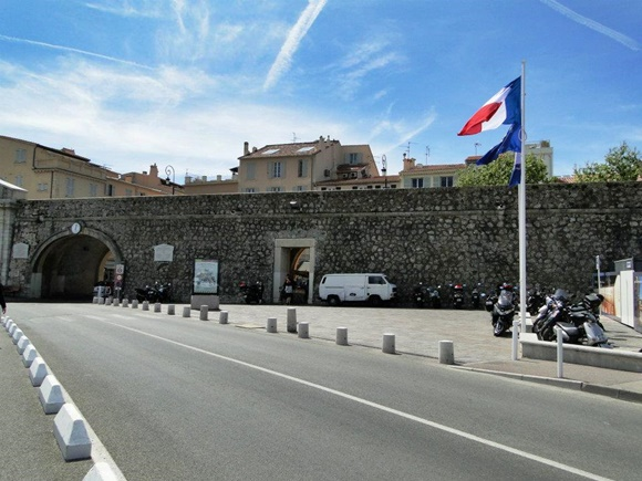 Muralha ao longe com passagem para o centro e bandeira da França hasteada à frente Blog Vem Por Aqui