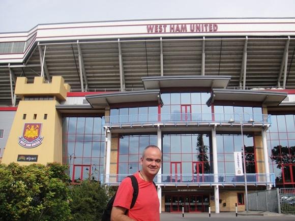 Fred em frente ao estádio com vidros na fachada e, acima, a inscrição West Ham United Blog Vem Por Aqui