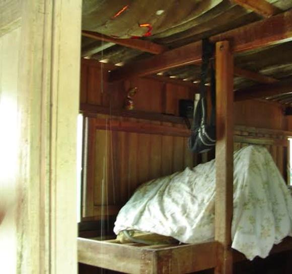 Cama de mandeira dentro do barco com colchão dobrado coberto com lençol Blog Vem Por Aqui