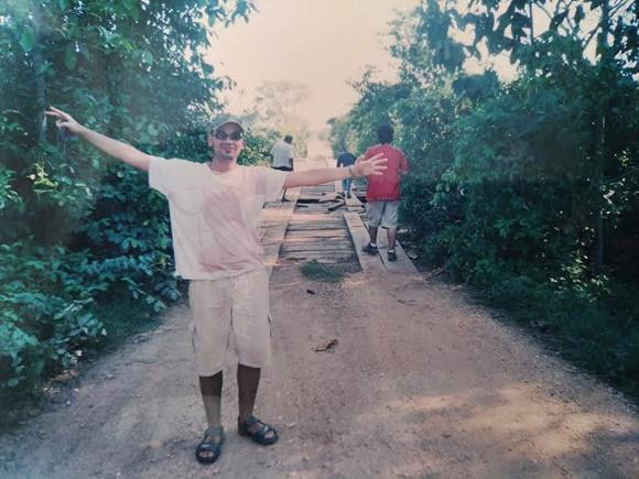 Fred, de braços abertos, na frente de uma ponte de madeira, no caminho pra Poconé Blog Vem Por Aqui