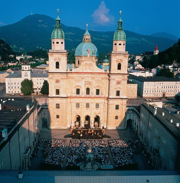 Praça com vários banquinhos cheios de pessoas e catedral imponente em frente Blog Vem Por Aqui