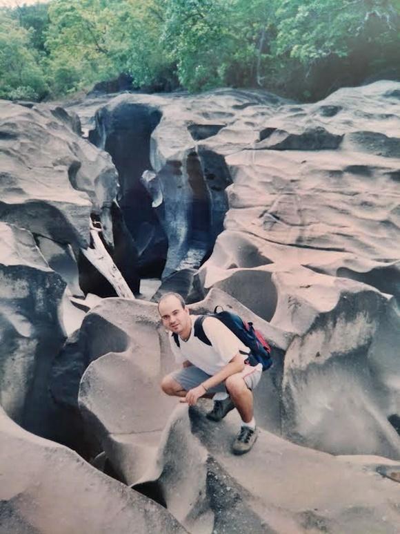 Fred abaixado no meio de uma rocha cheia de relevos na Chapada dos Veadeiros Blog Vem Por Aqui