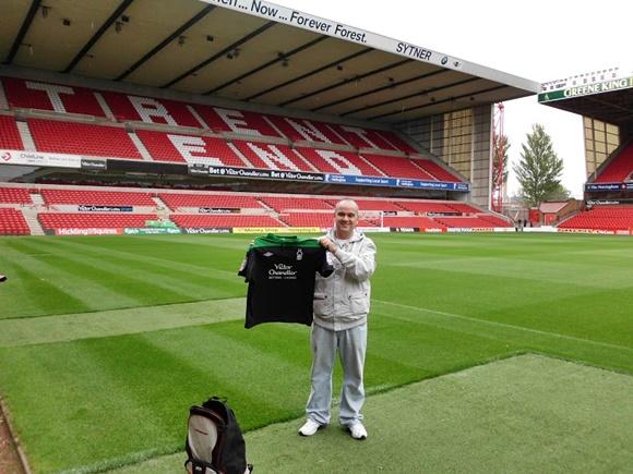 No gramado do estádio segurando a camisa que comprou lá com a mochila do lado Blog Vem Por Aqui