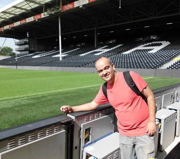 Fred de perfil, na lateral do campo, com grama ao lado e arquibancada com cadeiras pretas e Fulham escrito de branco ao fundo Blog Vem Por Aqui