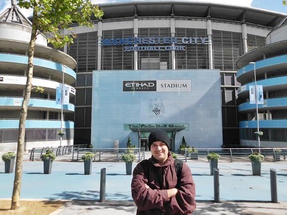 Fred de touca, casaco e braços cruzados em frente ao estádio, de onde se vê dois letreiros, o mais baixo Etihad Stadium e acima Manchester City Football Club Blog Vem Por Aqui