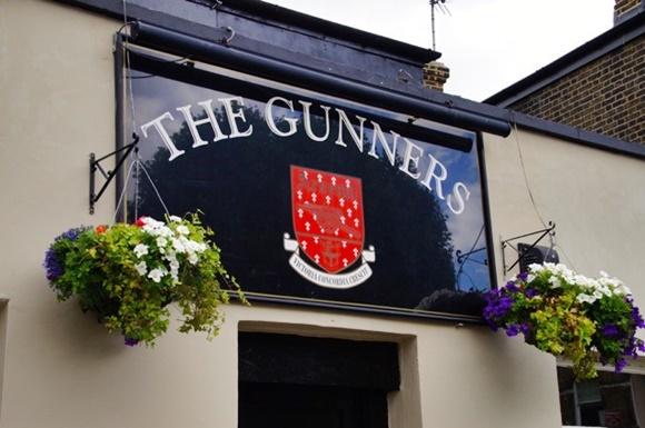 Fachada do The Gunners com placa em preto com o nome do pub e dois vasos de flores de cada lado Blog Vem Por Aqui