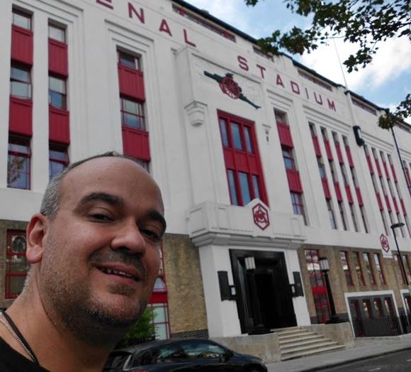 Fred em frente à antiga fachada do estádio pintada de vermelha e branco com escadaria na porta Blog Vem Por Aqui