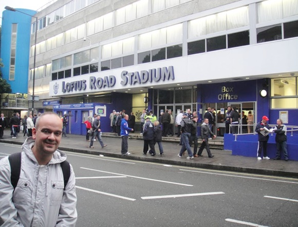 Fred diante do prédio do com pessoas passando na rua Blog Vem Por Aqui